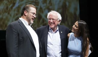 In this July 20, 2018, file photo, Democratic Kansas U.S. congressional candidate James Thompson, left, U.S Sen. Bernie Sanders, I-Vt., and Alexandria Ocasio-Cortez, a Democratic congressional candidate from New York, stand together on stage after a rally in Wichita, Kan. (Jaime Green/The Wichita Eagle via AP, File)
