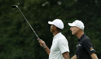 Jim Furyk, right, and Tiger Woods look at falling rain as they walk the first fairway during a practice round for the PGA Championship golf tournament Tuesday, Aug. 7, 2018, at Bellerive Country Club in St. Louis. (AP Photo/Charlie Riedel)