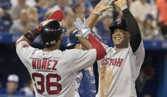Boston Red Sox'sRafael Devers high-fives with Eduardo Nunez after Devers hit a two-run home run during the sixth inning of a baseball game against the Toronto Blue Jays on Wednesday, Aug. 8, 2018, in Toronto. (Fred Thornhill/The Canadian Press via AP)