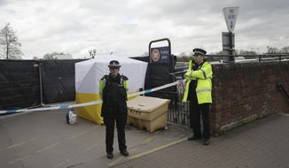 In this March 13, 2018, file photo, police officers guard a cordon around a police tent covering a supermarket car park pay machine near the spot where former Russian spy Sergei Skripal and his daughter were found critically ill following exposure to the Russian-developed nerve agent Novichok in Salisbury, England. The United States will impose sanctions on Russia for the country's use of a nerve agent in an assassination attempt on a former Russian spy and his daughter. The State Department says Aug. 8, sanctions will be imposed on Russia as the country used chemical or biological weapons in violation of international law.(AP Photo/Matt Dunham, File)