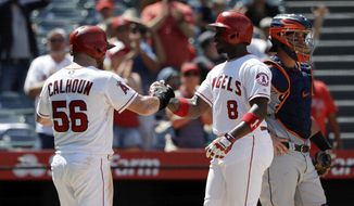 Los Angeles Angels' Justin Upton, center, is met at the plate by teammate Kole Calhoun (56) after hitting a two-run home run against the Detroit Tigers during the fifth inning of a baseball game Wednesday, Aug. 8, 2018, in Anaheim, Calif. (AP Photo/Marcio Jose Sanchez)