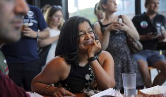 U.S. Rep. Pramila Jayapal listens as her campaign volunteers speak during a primary night event for Jayapal in the 7th congressional district race, Tuesday, Aug. 7, 2018 at Optimism Brewing in Seattle. (AP Photo/seattlepi.com, Genna Martin)