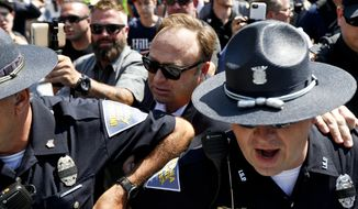 Alex Jones, center, an American conspiracy theorist and radio show host, is escorted out of a crowd of protesters after he said he was attacked in Public Square on Tuesday, July 19, 2016, in Cleveland, during the second day of the Republican convention. (AP Photo/John Minchillo)