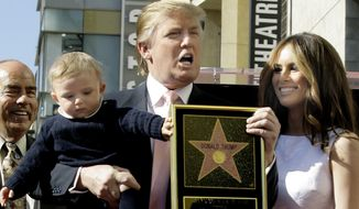"FILE - In this Tuesday, Jan. 16, 2007 file photo, Donald Trump, billionaire developer and producer of NBC's ""The Apprentice,"" with his wife, Melania, and their son, Barron, pose for a photo after he was given a star on the Hollywood Walk of Fame in Los Angeles. (AP Photo/Damian Dovarganes)"