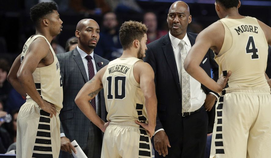 This photo from Nov. 28, 2017, shows Wake Forest assistant coach Jamill Jones, second from left, with the team and head coach Danny Manning, second from right, during the second half of an NCAA college basketball game in Winston-Salem, N.C. Police say Jones threw a punch that killed a New York City tourist who knocked on his car window thinking it was his Uber ride. He was arrested Thursday, Aug. 9, 2018, and charged with assault. (AP Photo/Chuck Burton)