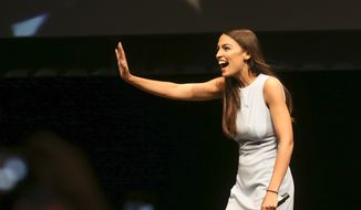 In this Friday, July 20, 2018, file photo, Alexandria Ocasio-Cortez, a Democratic congressional candidate from New York, waves during a rally, in Wichita, Kan. Ocasio-Cortez is trying to leverage the 17,000 votes that gave her a primary win in New York into a national movement. (Jaime Green/The Wichita Eagle via AP, File)