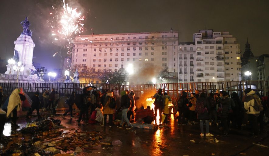 Pro-choice activists gather around a bonfire to keep warm as celebratory fireworks go off in the distance from a gathering of pro-life activists, as they all wait outside Congress for lawmakers to vote on an abortion bill in Buenos Aires, Argentina, early Thursday, Aug. 9, 2018. The Senate debated a bill that would legalize elective abortion in the first 14 weeks of pregnancy, and eventually voted against it, keeping abortion limited to cases of rape or risks to a woman's health. (AP Photo/Natacha Pisarenko)
