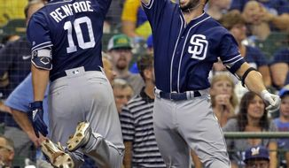 San Diego Padres' Hunter Renfroe, left, gets a high-five from Austin Hedges after Renfroe's grand slam against the Milwaukee Brewers during the ninth inning of a baseball game Thursday, Aug. 9, 2018, in Milwaukee. (AP Photo/Jeffrey Phelps)