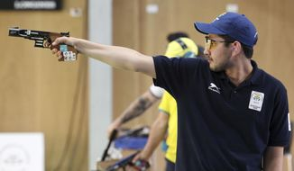 In this April 13, 2018, file photo, Anish Bhanwala of India shoots during the men's 25m Rapid Fire Pistol final at the Belmont Shooting Centre during the 2018 Commonwealth Games in Brisbane, Australia. At 15 and still at high school, Anish was India's youngest gold medalist at the Commonwealth Games on Australia's Gold Coast in April when he won the 25-meter rapid fire pistol shooting event in a meet record. (AP Photo/Tertius Pickard, File)
