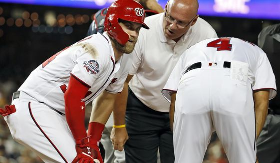 Washington Nationals' Bryce Harper, left, is attended to by trainer Paul Lessard and manager Dave Martinez, after he was hit on the leg by a pitch during the seventh inning of the team's baseball game against the Atlanta Braves at Nationals Park, Wednesday, Aug. 8, 2018, in Washington. The Braves won 8-3. (AP Photo/Alex Brandon) **FILE**