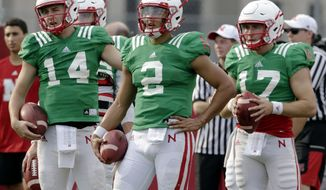 Nebraska quarterbacks Adrian Martinez (2), Tristan Gebbia (14) and Andrew Bunch (17) stand together during NCAA college football fall practice in Lincoln, Neb., Wednesday, Aug. 8, 2018. Nebraska's three-man quarterback race remains too close to call. Quarterbacks coach Mario Verduzco says Martinez, Gebbia and Bunch continue to get an equal number of snaps with the first-string offense. (AP Photo/Nati Harnik)