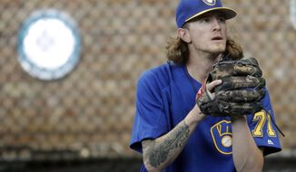 FILE - In this July 20, 2018, file photo, Milwaukee Brewers relief pitcher Josh Hader warms up before a baseball game against the Los Angeles Dodgers in Milwaukee. Whatever progress baseball has made promoting inclusion, it took a backseat recently. Years-old racist, misogynist and homophobic tweets from Milwaukee reliever Josh Hader were found during the All-Star Game.  (AP Photo/Morry Gash, File)