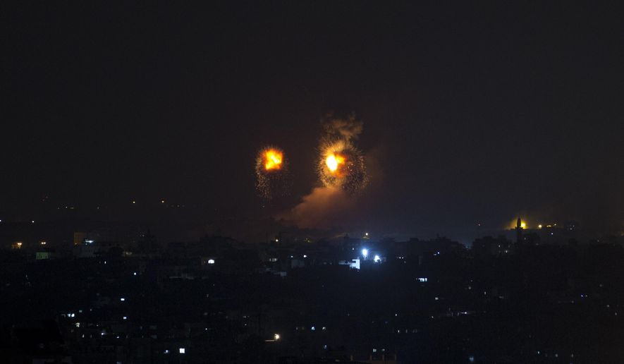 Fire balls caused by Israeli airstrikes on Gaza City, early Thursday, Aug. 9, 2018.  Israel struck targets in the Gaza Strip after dozens of rockets were launched Wednesday from the coastal territory ruled by the Islamic militant Hamas group, the Israeli military said.(AP Photo/Khalil Hamra)