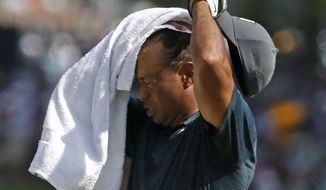 Tiger Woods wipes sweat from his face on the 17th hole during the first round of the PGA Championship golf tournament at Bellerive Country Club, Thursday, Aug. 9, 2018, in St. Louis. (AP Photo/Brynn Anderson)