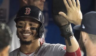 Boston Red Sox's Mookie Betts is congratulated in the dugout after scoring against the Toronto Blue Jays during the first inning of a baseball game Thursday, Aug. 9, 2018, in Toronto. (Fred Thornhill/The Canadian Press via AP)