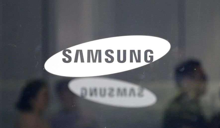 In this July 31, 2018, file photo employees walk past logos of the Samsung Electronics Co. at its office in Seoul, South Korea. Samsung is expected to unveil a new phone on Thursday, Aug. 9, 2018. (AP Photo/Ahn Young-joon, File)