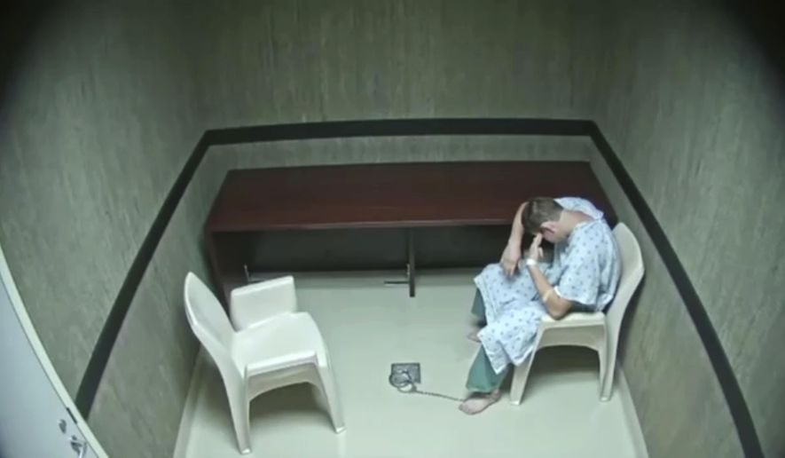 In this image made from video provided on Wednesday, Aug. 8, 2018, by the Broward County Sheriff's Office, Nikolas Cruz points his fingers to his temple at an interrogation room, while officers are out of the room, in Fort Lauderdale, Fla. Prosecutors on Wednesday released hours of video interrogation of Florida's school shooting suspect, footage showing the young man slouching in a chair, being repeatedly urged by a detective to speak louder and punching himself in the face when he is alone. (Broward County Sheriff's Office via AP)