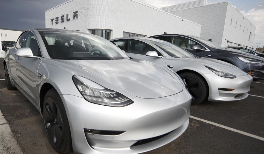 FILE- In this July 8, 2018, file photo, 2018 Model 3 sedans sit on display outside a Tesla showroom in Littleton, Colo. On Thursday, Aug. 9, Tesla shares have dropped back to near the level they were trading at before CEO Elon Musk tweeted Tuesday that he may take the company private. (AP Photo/David Zalubowski, File)