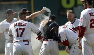 Cleveland Indians teammates mob Michael Brantley after he hit the game-winning RBI-single in the ninth inning of a baseball game against the Minnesota Twins, Thursday, Aug. 9, 2018, in Cleveland. Greg Allen scored on the play. The Indians won 5-4. (AP Photo/Tony Dejak)