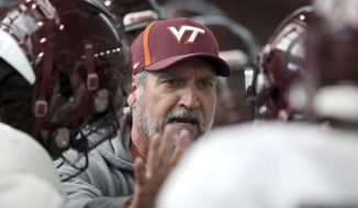 FILE - In this March 22, 2018, file photo, Virginia Tech defensive coordinator Bud Foster talks to players during spring NCAA college football practice in Blacksburg, Va. Virginia Tech is spending much of fall practice working to fill some huge and unexpected holes on defense.  (Matt Gentry/The Roanoke Times via AP)