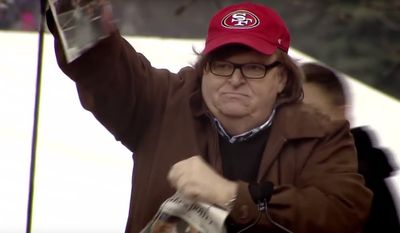 """Filmmaker Michael Moore rips a newspaper with President Trump's visage on the front page during the trailer for his new """"Fahrenheit11/9"""" documentary. (Image: YouTube, Michael Moore)"""