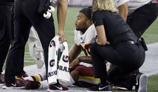 Washington Redskins running back Derrius Guice, center, receives attention on the field after an injury during the first half of a preseason NFL football game against the New England Patriots, Thursday, Aug. 9, 2018, in Foxborough, Mass. (AP Photo/Steven Senne)
