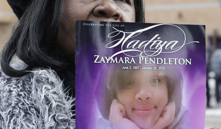 FILE - In this Feb. 9, 2013, file photo, a mourner holds up a funeral program for Hadiya Pendleton, outside the Greater Harvest Missionary Baptist Church during the funeral service. Jury selection begins Friday, Aug. 10, 2018, in the trial of two men charged in the fatal shooting in January 2013 of Pendleton, a 15-year-old Chicago student just days after she performed with her high school band at then-President Barack Obama's inaugural festivities. (AP Photo/Nam Y. Huh, File)