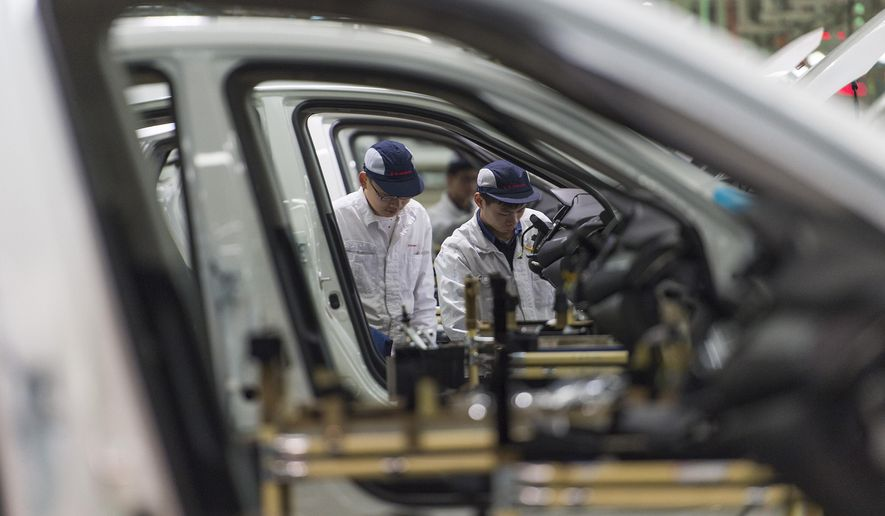 In this Feb. 6, 2017, photo, workers assemble cars at the Dongfeng Honda automotive plant in Wuhan in central China's Hubei province. China's auto sales shrank by 5.3 percent in July 2018 from a year earlier as SUV demand sagged, adding to signs of economic malaise amid a tariff battle with Washington. (Chinatopix via AP)