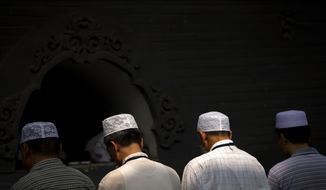 FILE - In this July 18, 2015, file photo, Chinese Hui Muslims pray during Eid al-Fitr prayers at Niujie Mosque in Beijing. Authorities in northwestern China were poised to begin demolition of a mosque Friday, Aug. 10, 2018, despite protests by hundreds of members of the country's Muslim Hui ethnic minority determined to preserve the newly built structure. (AP Photo/Mark Schiefelbein, File)