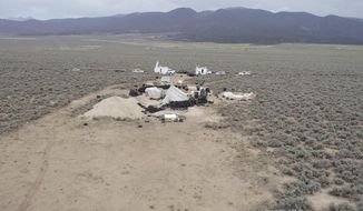 This aerial image shows a remote outpost near Amalia, N.M on Thursday, Aug. 9, 2018.  Three siblings and two other adults have been charged with child abuse stemming from the alleged neglect of 11 children found living on the squalid compound. All five are being jailed without bail in New Mexico.  (Karl Brennan/DroneBase via AP)