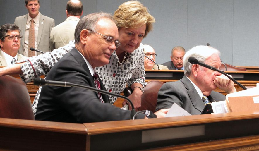 Rep. Tony Bacala, R-Prairieville, left, talks with Sen. Sharon Hewitt, R-Slidell, about financial data during a meeting of the Joint Legislative Committee on the Budget, on Friday, Aug. 10, 2018, in Baton Rouge, La. (AP Photo/Melinda Deslatte)