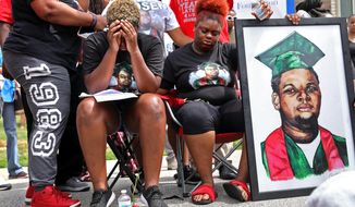 Trinetta, center left, 19, and Triniya Brown become emotional during a memorial service for their brother, Michael Brown, on Thursday, Aug. 9, 2018, in the Canfield Green apartment complex in Ferguson, Mo., where Brown was shot and killed by former Ferguson police officer Darren Wilson four years ago. (Cristina M. Fletes/St. Louis Post-Dispatch via AP)