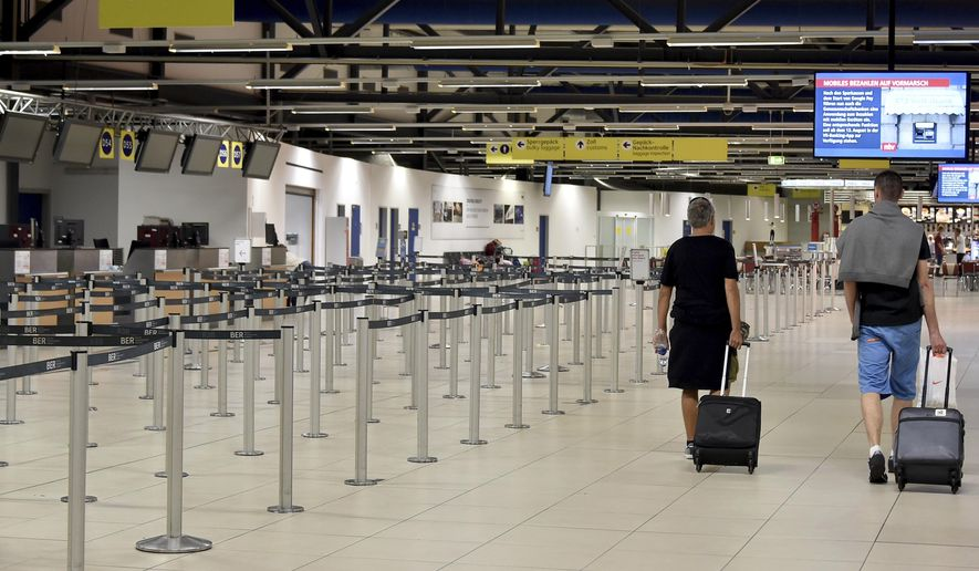 Passenger walk through the empty departure hall of the Schoenefeld airport near Berlin Friday, Aug. 10, 2018 when several flights of Irish Ryanair airline had been cancelled due to a strike of pilots. (Bernd Settnik/dpa via AP)