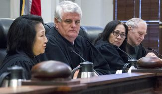 FILE - In this Feb. 2, 2017, file photo, from left, Justice Paula Nakayama, Chief Justice Mark Recktenwald and Justices Sabrina McKenna and Michael Wilson preside at a hearing before the Hawaii Supreme Court in Honolulu. Hawaii Supreme Court Justice Michael Wilson weighing the fate of a controversial giant telescope says he received emails from a land board member who voted in favor of the project. Justice Wilson filed a notice saying he didn't read the emails he received from Sam Gon last month. The notice reminds those involved in the case that communicating with justices is prohibited. (Craig T. Kojima/The Star-Advertiser via AP, Pool, File)