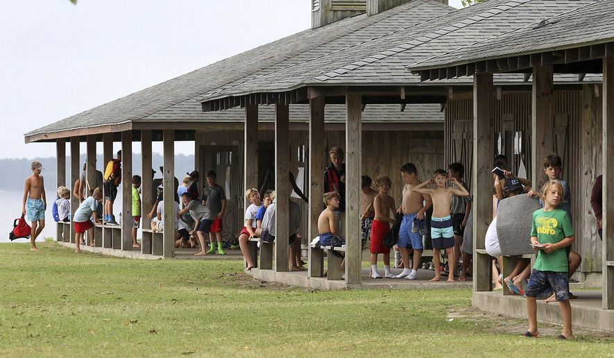 FILE- In this July 20, 2018, file photo, children gather at their respective cabins and get ready for the day's activities during a four-week summer camp session at Camp Sea Gull near Arapahoe, N.C. About 90 percent of the nearly 8,400 sleep away camps counted by the American Camp Association are now device free, though some allow limited time with screenless iPods and other internet-free music players. (Gray Whitley/Sun Journal via AP, File)