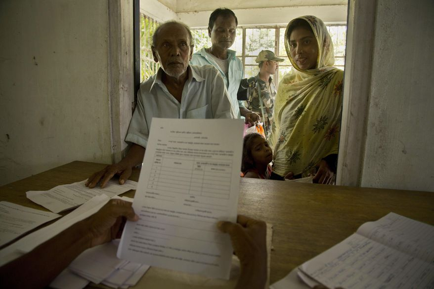 People whose names were left out in the National Register of Citizens (NRC) draft stand to collect forms to file appeals in Mayong, 45 kilometers (28 miles) east of Gauhati, India, Friday, Aug. 10, 2018. A draft list of citizens in Assam, released in July, put nearly 4 million people on edge to prove their Indian nationality. Nativist anger churns through Assam, just across the border from Bangladesh, with many believing the state is overrun with illegal migrants. (AP Photo/Anupam Nath)