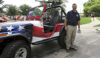 FILE - This June 2, 2018, file photo provided by the Kobach for Governor campaign shows Kansas Secretary of State Kris Kobach, a Republican candidate for governor, posing next to a Jeep mounted with a replica machine gun at the Old Shawnee Days Parade in Shawnee, Kan. Kobach, the state's top election official, is locked in a too-close-to-call race for the GOP nomination with Gov. Jeff Colyer. (Danedri Herbert/Kobach for Governor campaign via AP, File)