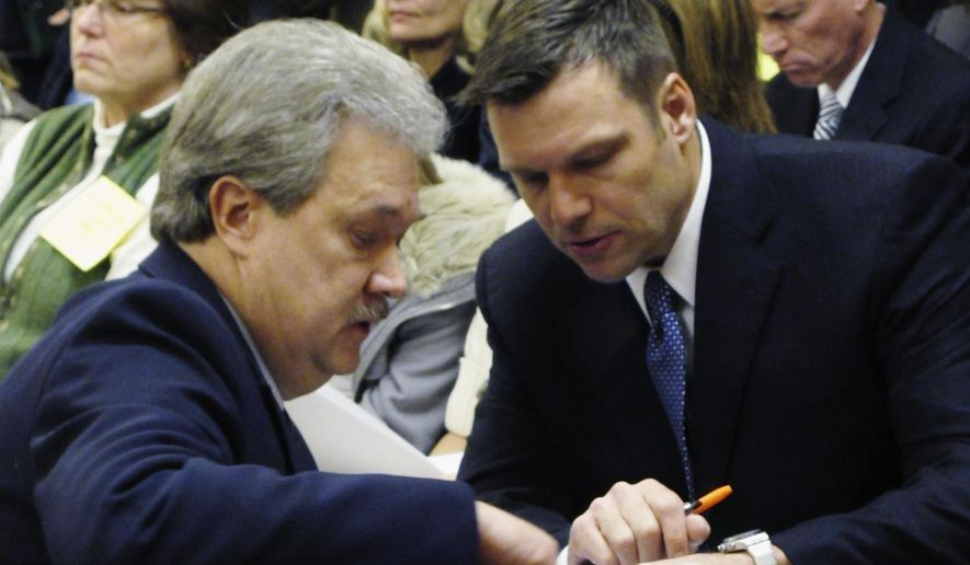 FILE - In this Jan. 31, 2011, file photo, Kansas Secretary of State Kris Kobach, right, confers with Assistant Secretary of State Eric Rucker during a Kansas House Elections Committee hearing on Kobach's bill for cracking down on election fraud at the Statehouse in Topeka, Kan. Kobach says he's stepping aside from his duties as the state's top elections official while his hotly contested Republican primary race with Gov. Jeff Colyer remains unresolved. Kobach announced his decision Friday, Aug. 10, 2018, in a letter to Colyer. Kobach said he is handing his election duties over to Rucker. (AP Photo/John Hanna, File)