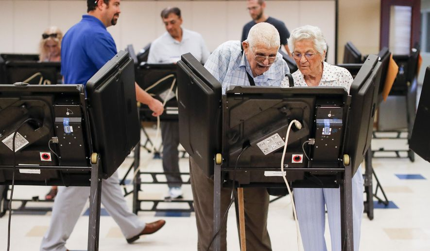 In this Aug. 7, 2018, photo, voters cast their ballots among an array of electronic voting machines in a polling station at the Noor Islamic Cultural Center, Tuesday, Aug. 7, 2018, in Dublin, Ohio. An Associated Press analysis find Democrats with a consistent enthusiasm advantage with nearly a dozen federal special elections now concluded ahead of the November midterms. (AP Photo/John Minchillo)