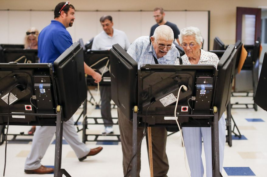 In this Aug. 7, 2018, file photo, voters cast their ballots among an array of electronic voting machines in a polling station at the Noor Islamic Cultural Center, Tuesday, Aug. 7, 2018, in Dublin, Ohio. (AP Photo/John Minchillo) ** FILE **