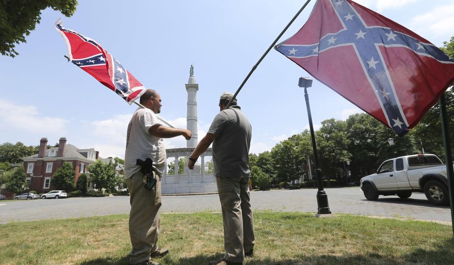 In this Thursday, June 25, 2015, photo, activists hold Confederate flags near the monument for Confederate President Jefferson Davis on Monument Avenue in Richmond, Va. (AP Photo/Steve Helber) ** FILE* *
