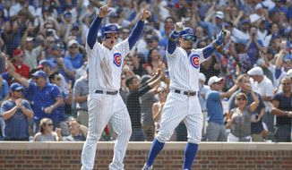 Chicago Cubs' Anthony Rizzo, left, and Javier Baez, right, celebrate after scoring on single hit by Jason Heyward against the Washington Nationals during the sixth inning of a baseball game, Friday, Aug. 10, 2018, in Chicago. (AP Photo/Kamil Krzaczynski)