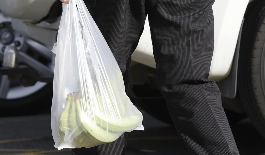 In this file photo, a shopper leaves a supermarket with goods in plastic bags in Christchurch, New Zealand, Friday, Aug. 10, 2018. On April 23, 2019, Oklahoma Gov. Kevin Stitt signed legislation to prevent cities and towns in the state from placing a fee on single-use grocery bags. (AP Photo/Mark Baker) **FILE**