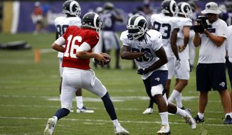 Los Angeles Rams running back Todd Gurley, right, runs a drill with quarterback Jared Goff during a joint NFL football training camp practice at the Baltimore Raven's headquarters, Tuesday, Aug. 7, 2018, in Owings Mills, Md. (AP Photo/Patrick Semansky)