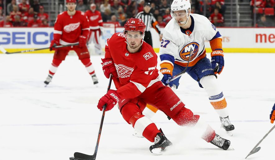 File-This April 7, 2018, file photo shows Detroit Red Wings center Dylan Larkin (71) skating past New York Islanders left wing Anders Lee (27) in the second period of an NHL hockey game in Detroit. The Detroit Red Wings have re-signed Larkin to a $30.5 million, five-year contract. The team announced the deal with the 22-year-old center on Friday. Larkin was a restricted free agent. He led the team with a career-high 63 points and was third with 16 goals last season. He has 56 goals and 140 points over three NHL seasons, playing in at least 80 games each year. (AP Photo/Paul Sancya, File)