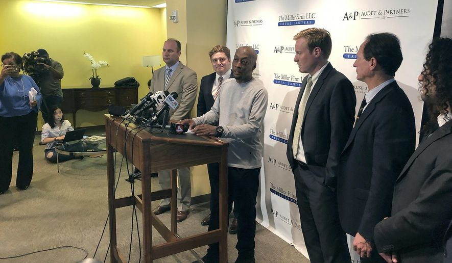 Plaintiff Dewayne Johnson, center at podium, surrounded by his attorneys, takes questions from the media after the Monsanto trial in San Francisco Friday, Aug. 10, 2018. A San Francisco jury ordered agribusiness giant Monsanto to pay $289 million to the former school groundskeeper dying of cancer, saying the company's popular Roundup weed killer contributed to his disease. The lawsuit brought by Johnson was the first to go to trial among hundreds filed in state and federal courts saying Roundup causes non-Hodgkin's lymphoma, which Monsanto denies. (AP Photo/Paul Elias)