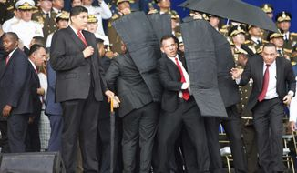 Security personnel surrounded Venezuelan President Nicolas Maduro when an explosive-laden drone disrupted a military parade in Caracas last week. Various groups purporting to represent former and active members of Venezuela's armed forces have claimed responsibility, and some opposition leaders say the assassination attempt was a hoax engineered by the regime to justify an even greater crackdown on dissent. (Associated Press/File)