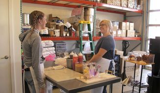 In this photo taken June 8, 2018, craft donut shop owner Amy Pruchnic, right, talks with an employee at her busy new store in downtown Spokane, Wash. The state's second-largest city is booming these days thanks to a good economy and influx of new residents. (AP Photo/Nicholas K. Geranios)