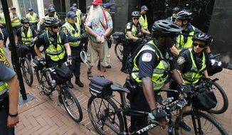 State Police escort local resident, John Miska, red hat, after he was arrested in the locked down downtown area in Charlottesville, Va., Saturday, Aug. 11, 2018. Miska purchased razor blades, which are banned items, in a downtown drugstore. On the the anniversary of white supremacist violence, state and local authorities framed the weekend's heightened security as a necessary precaution. (AP Photo/Steve Helber)