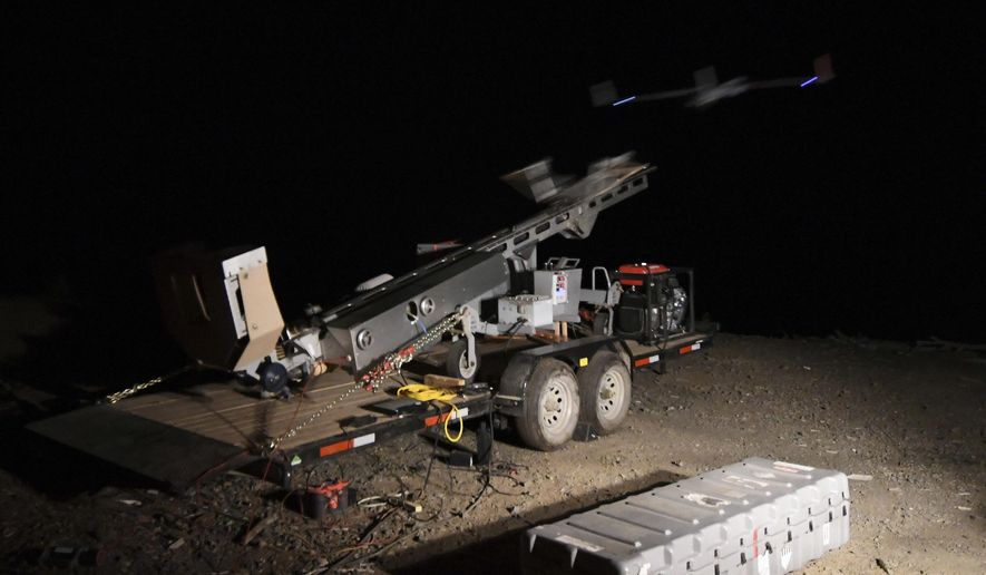 In this Tuesday, Aug. 7, 2018 photo, after the ScanEagle unmanned aircraft is loaded onto the launcher and a series of pre-flight checks are carried out, the pneumatic slingshot sends the 44-pound drone into the night sky near Azalea, Ore. The aircraft, equipped with an infrared camera, flew for more than seven hours that night while detecting hotspots over the Taylor Creek Fire in Southwest Oregon. (Scott Stoddard/The Daily Courier via AP)